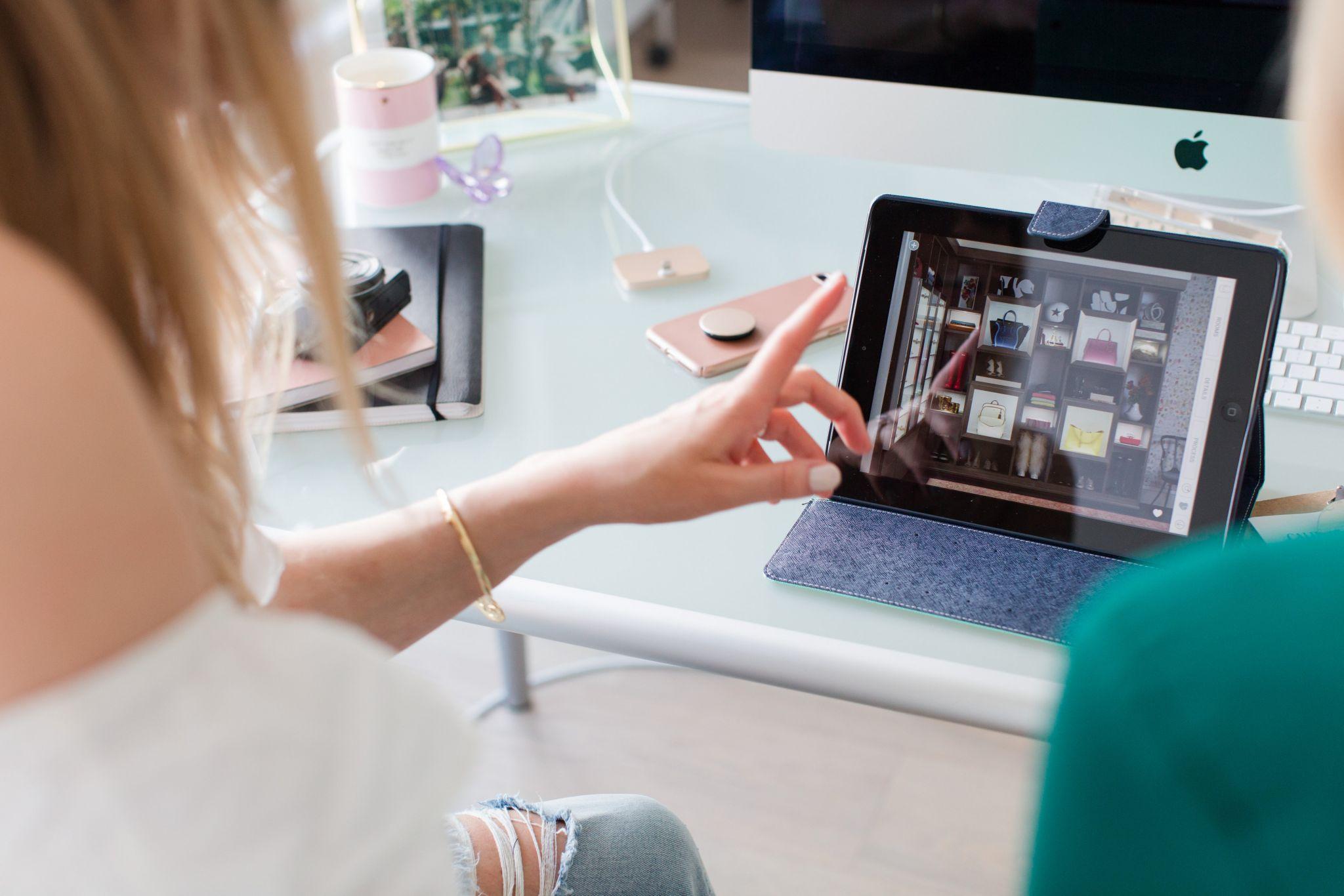 2 girls sitting at a computer desk, California closet design consultation, iPad with example of closet options