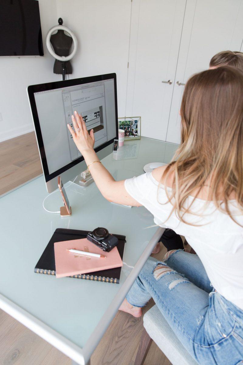 1 girl sitting at desk, pointing to computer, iMac blogger desk