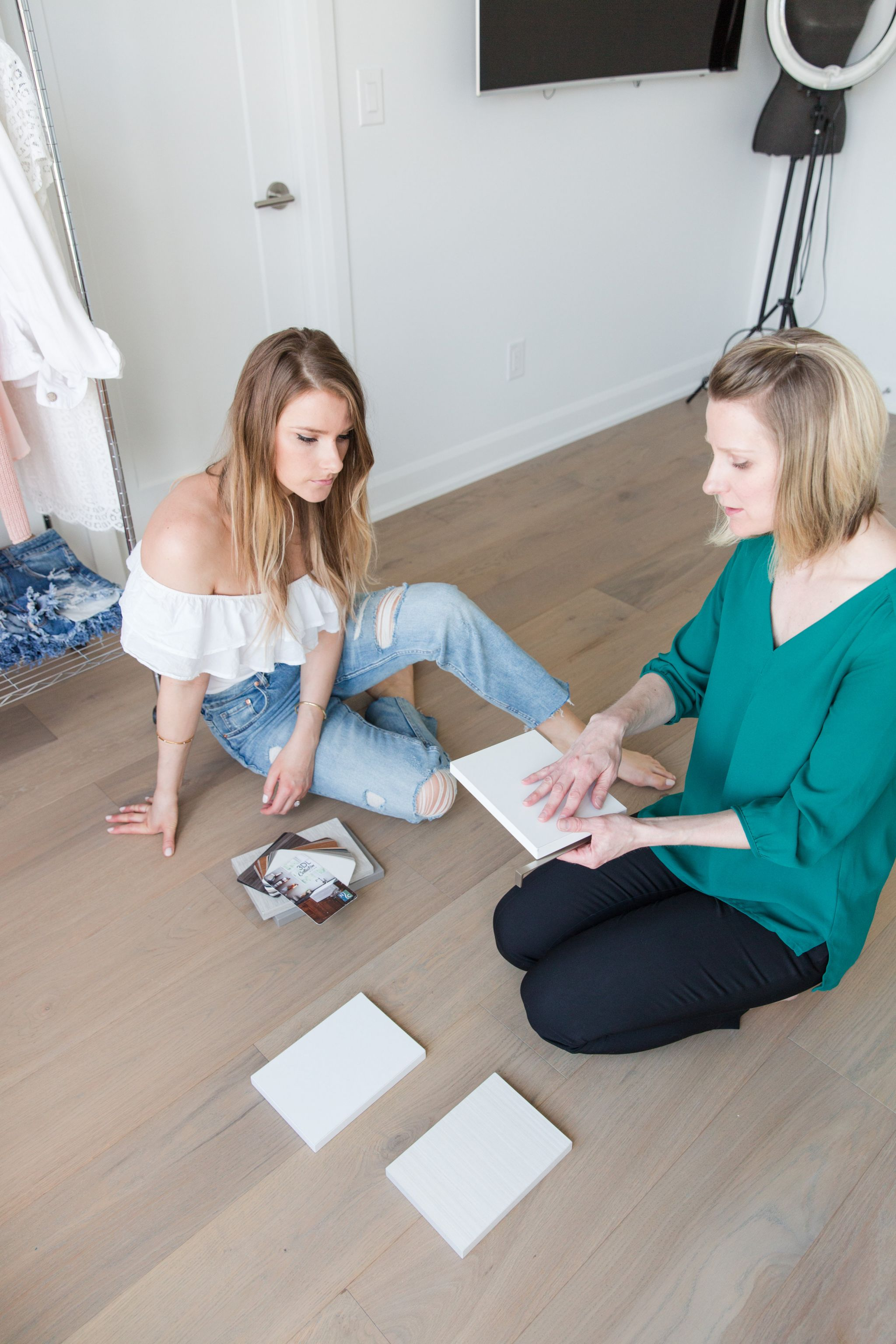 2 girls sitting on the floor, looking at closet samples and drawer handles