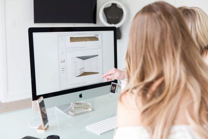 blogger sitting at desk, looking at design mock ups on computer from California closets