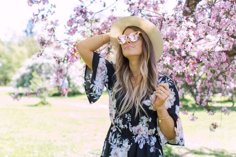 1 person, fashion blogger walking in park amongst cherry blossom trees, girl wearing floral romper