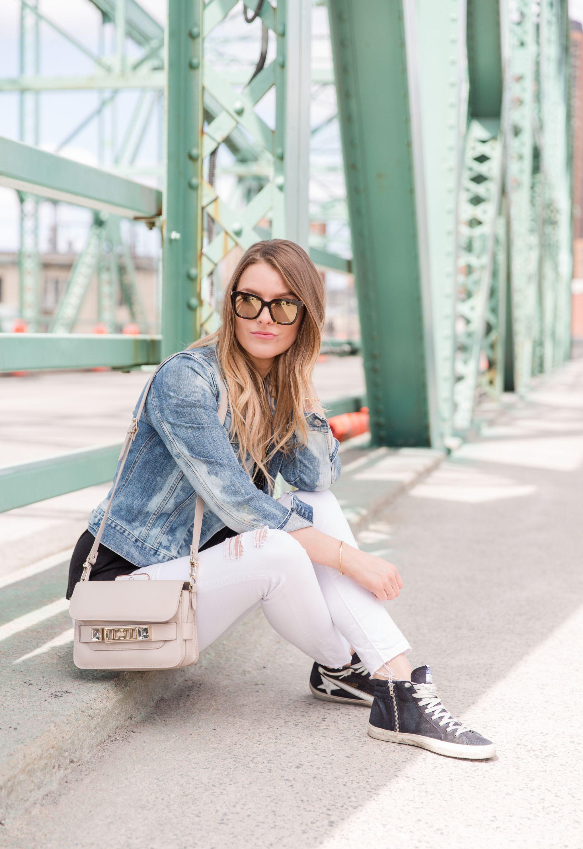 I person, sitting on a bridge, wearing a jean jacket