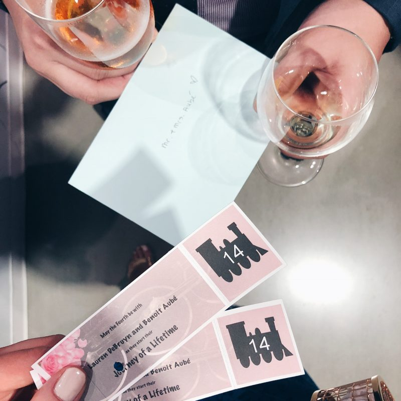 wedding tickets, two glasses of wine