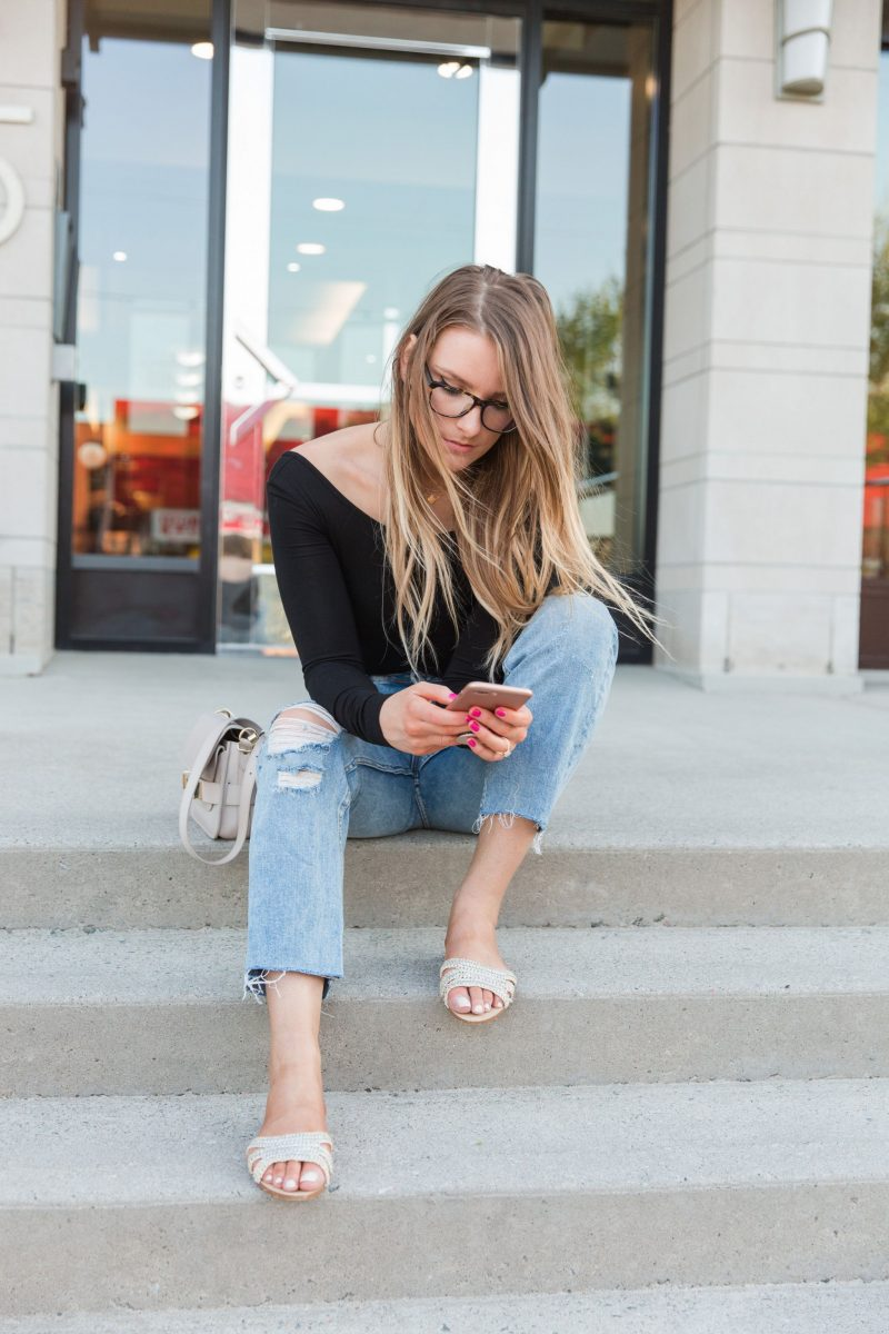 1 person, sitting on steps outside, jeans and bodysuit outfit