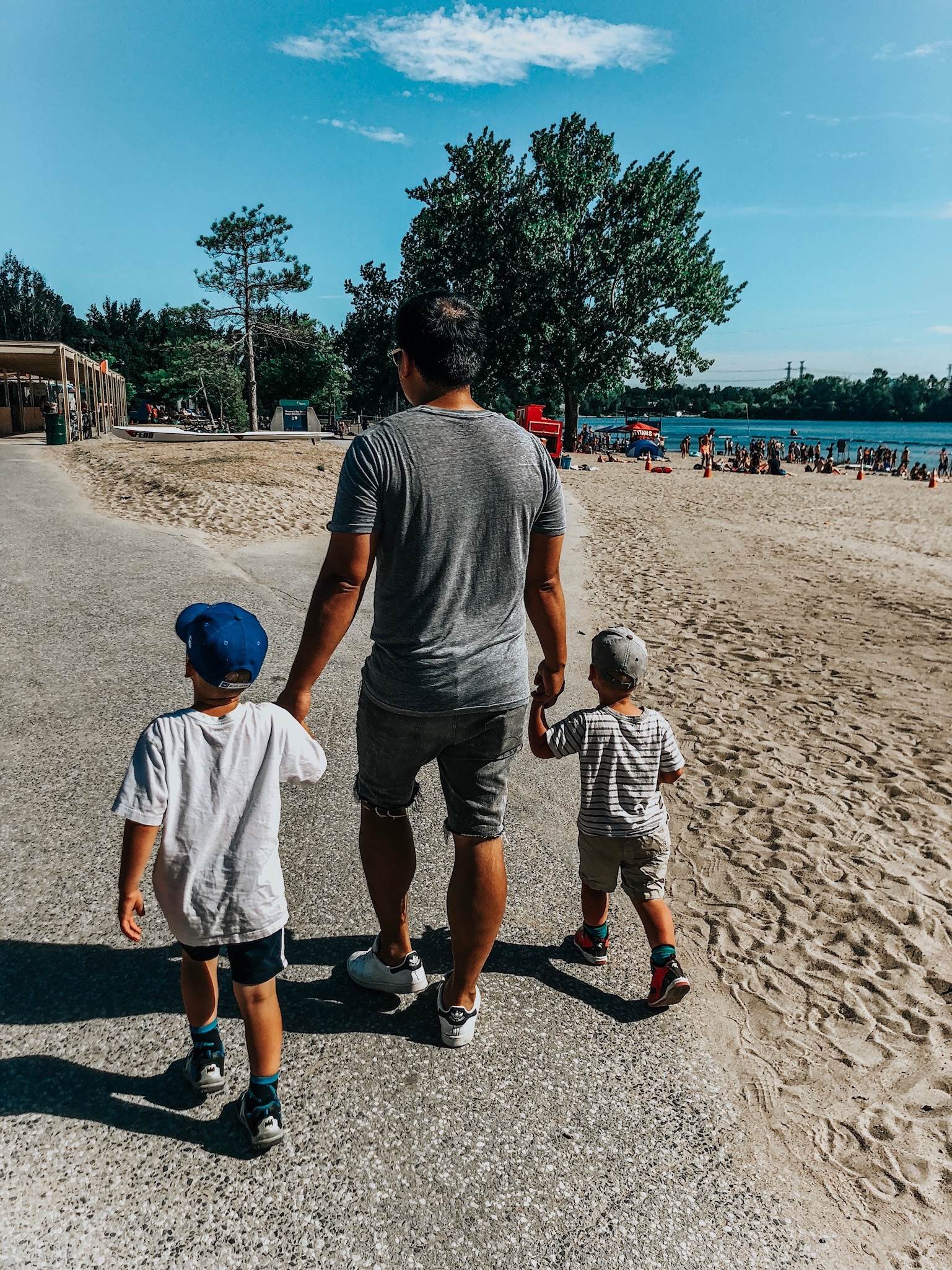 cute dad with two boys at the beach