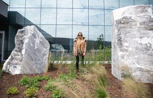 1 person, girl standing between large rocks