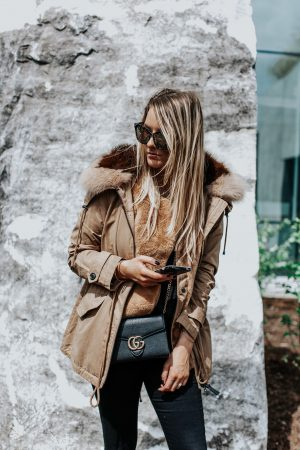 1 person, tan anorak jacket with fur collar and gucci bag