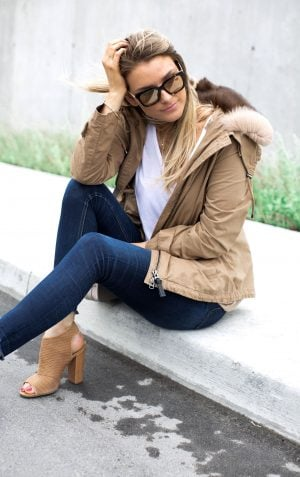 1 person sitting on a curb, girl wearing fur collar jacket