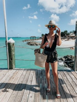 1 person, standing on pier in bahamas in swimsuit and hat