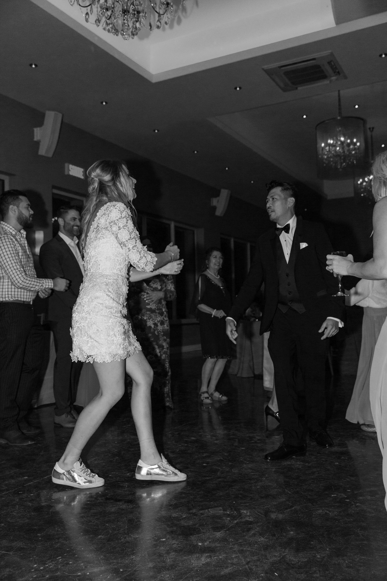 bride dancing in short white dress and sneakers