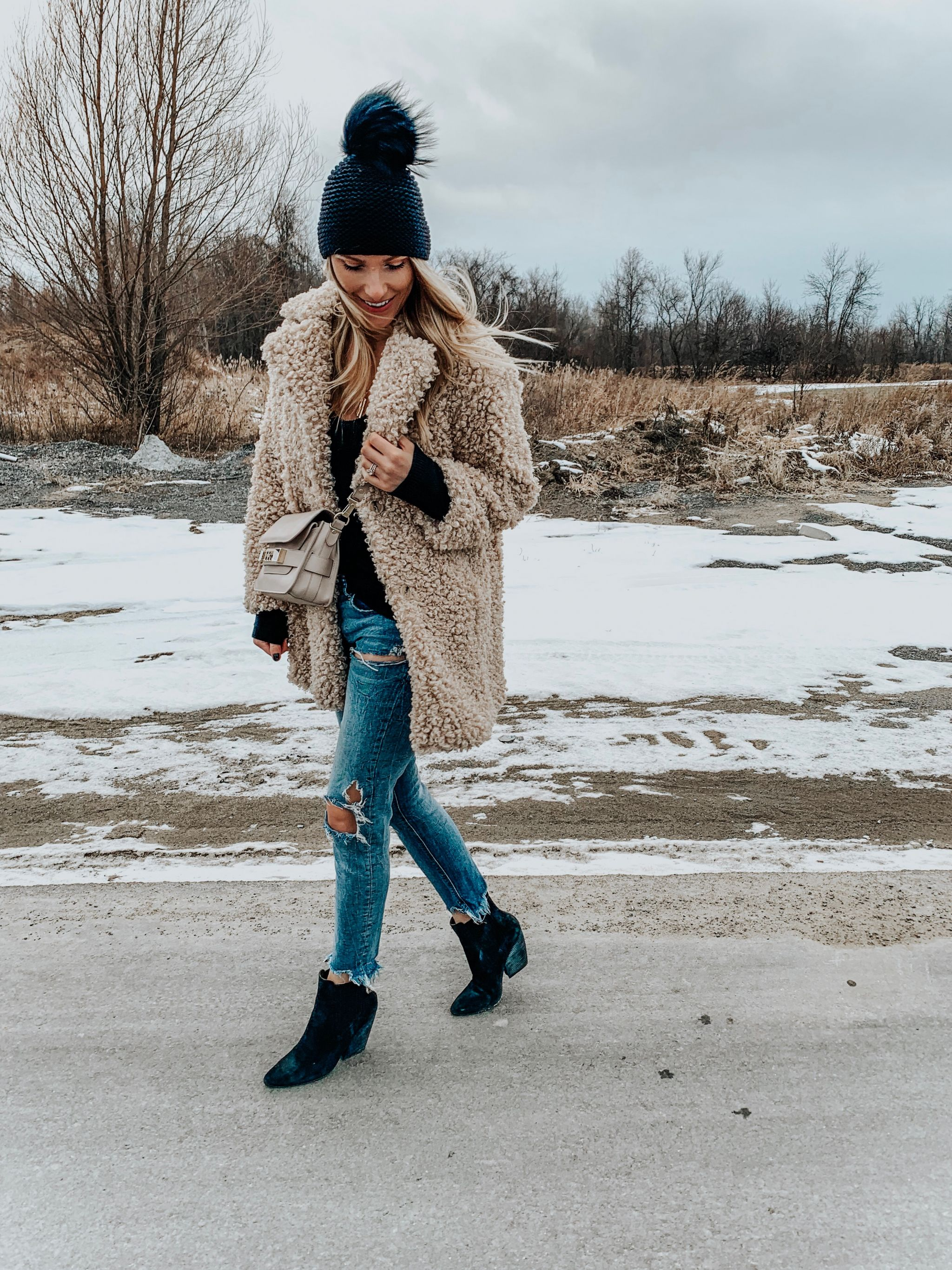 1 girl wearing teddy coat and ripped jeans
