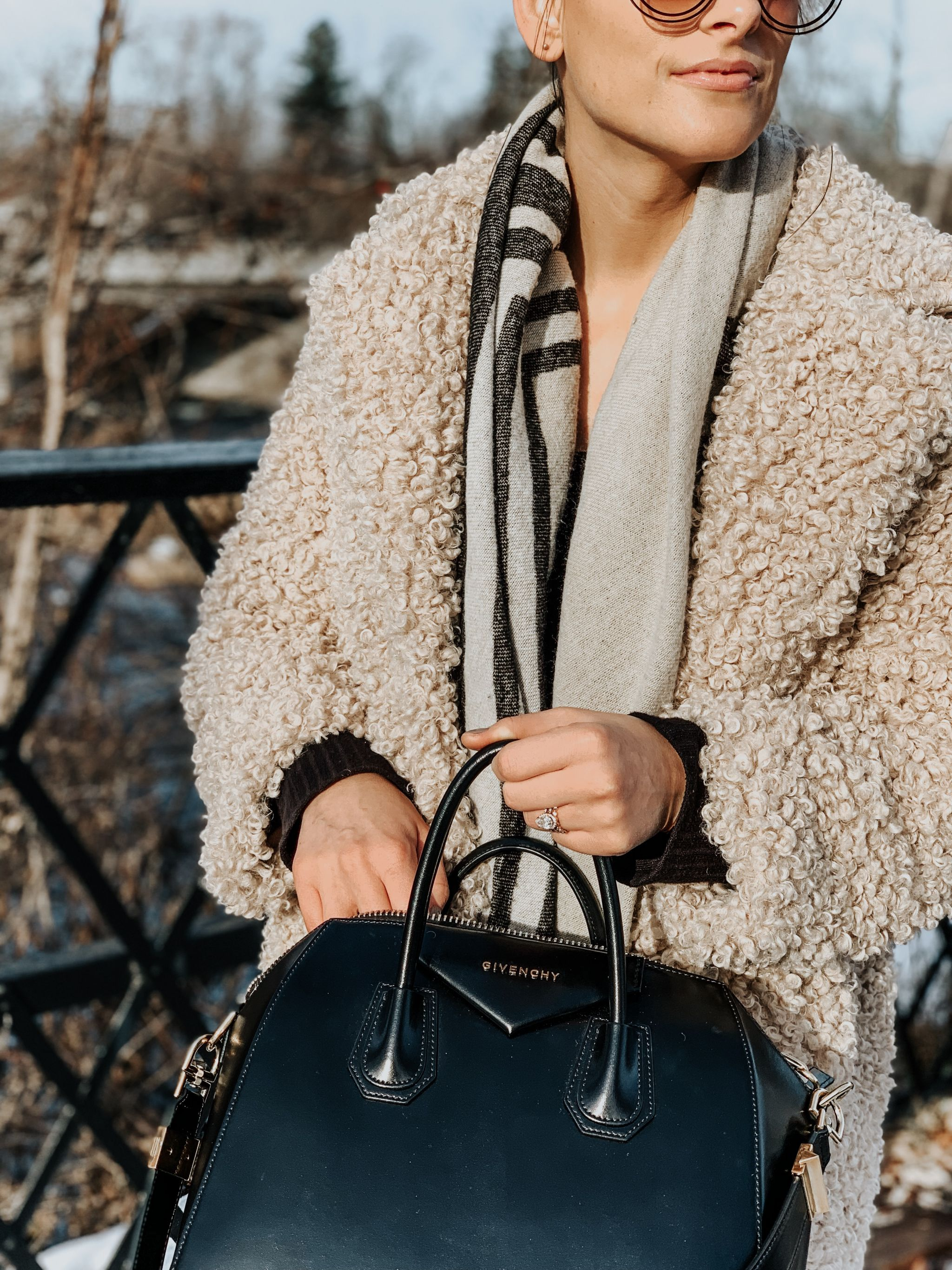 girl holding givenchy antigona bag and wearing teddy coat