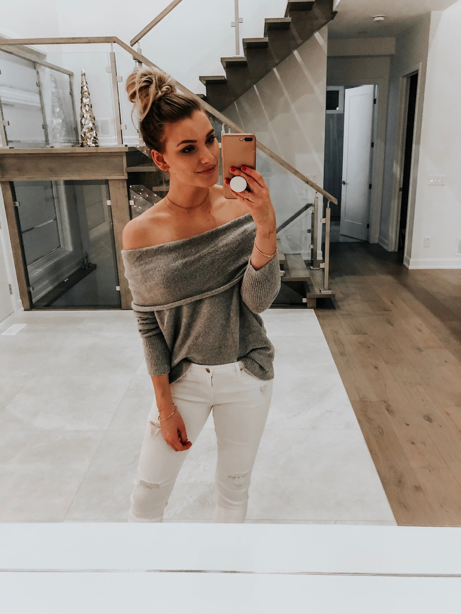 girl wearing off shoulder grey sweater and white jeans taking a selfie