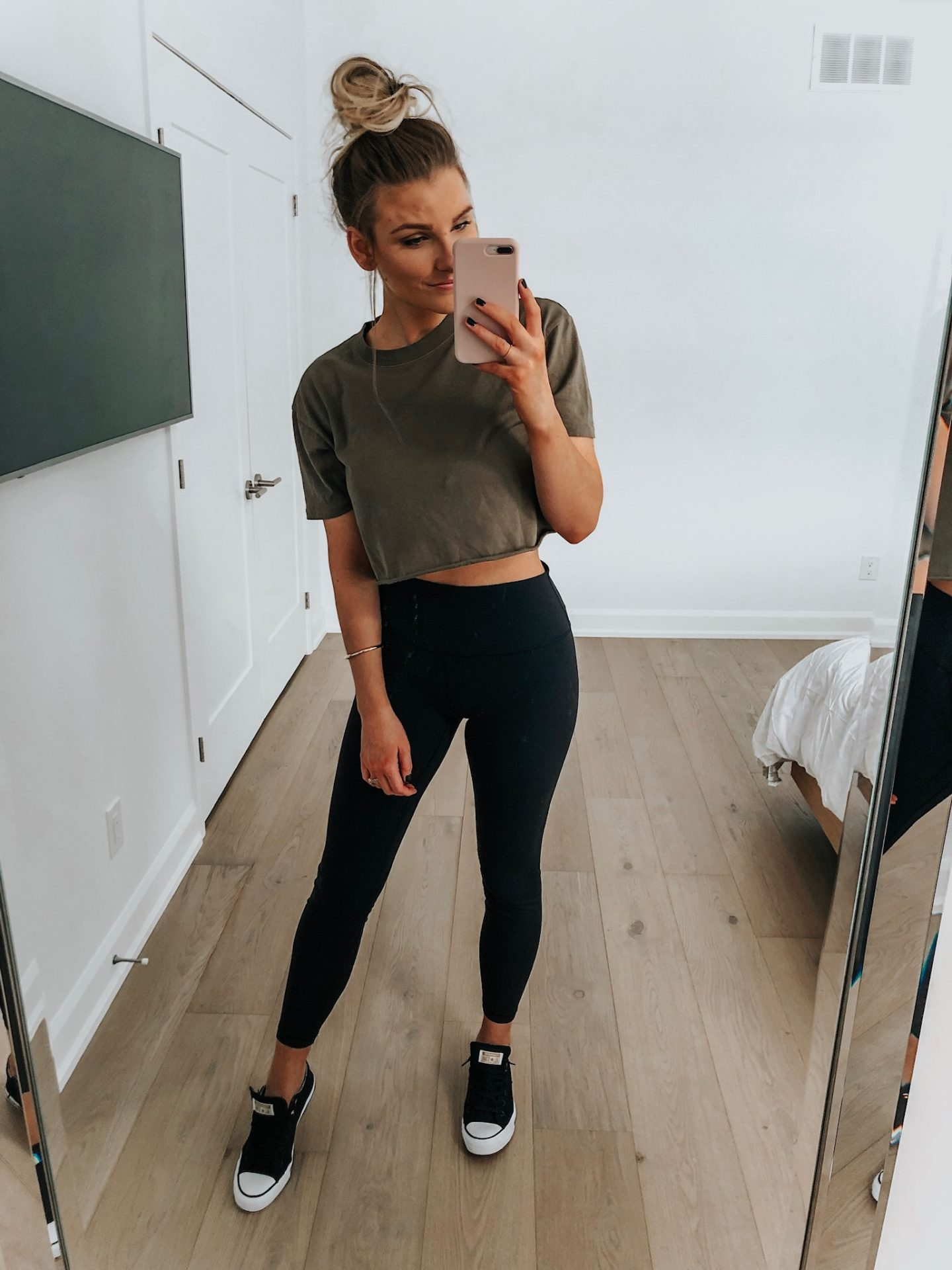 fashion blogger taking selfie wearing green crop top and black leggings with converse