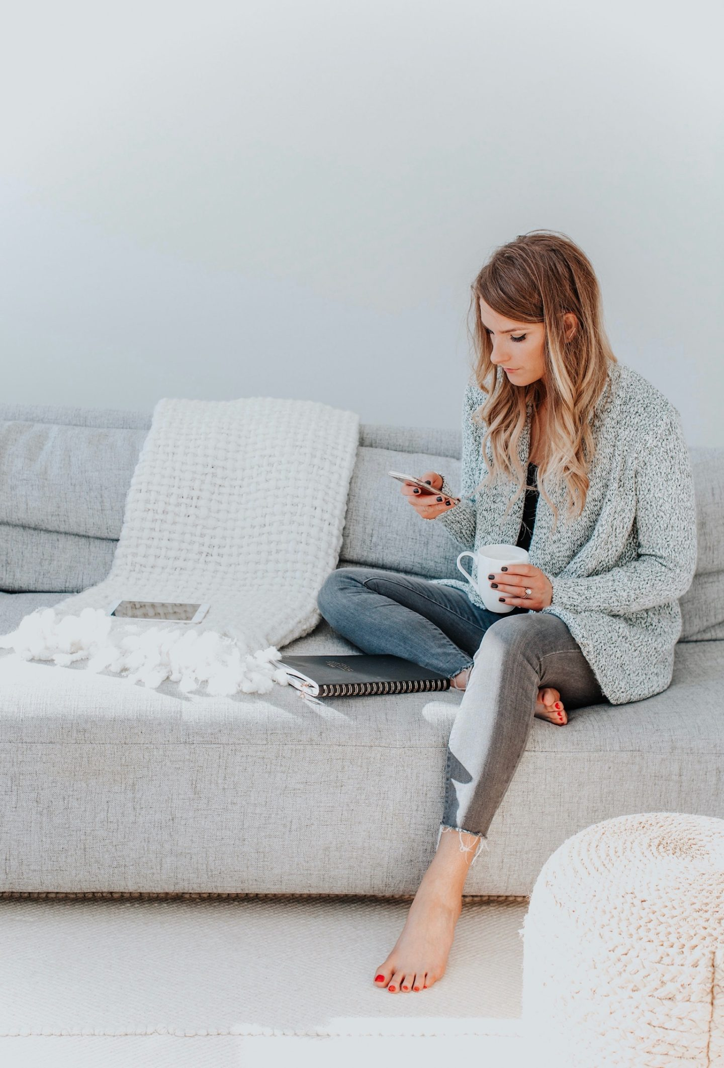 girl sitting on couch looking at phone with coffee in hand