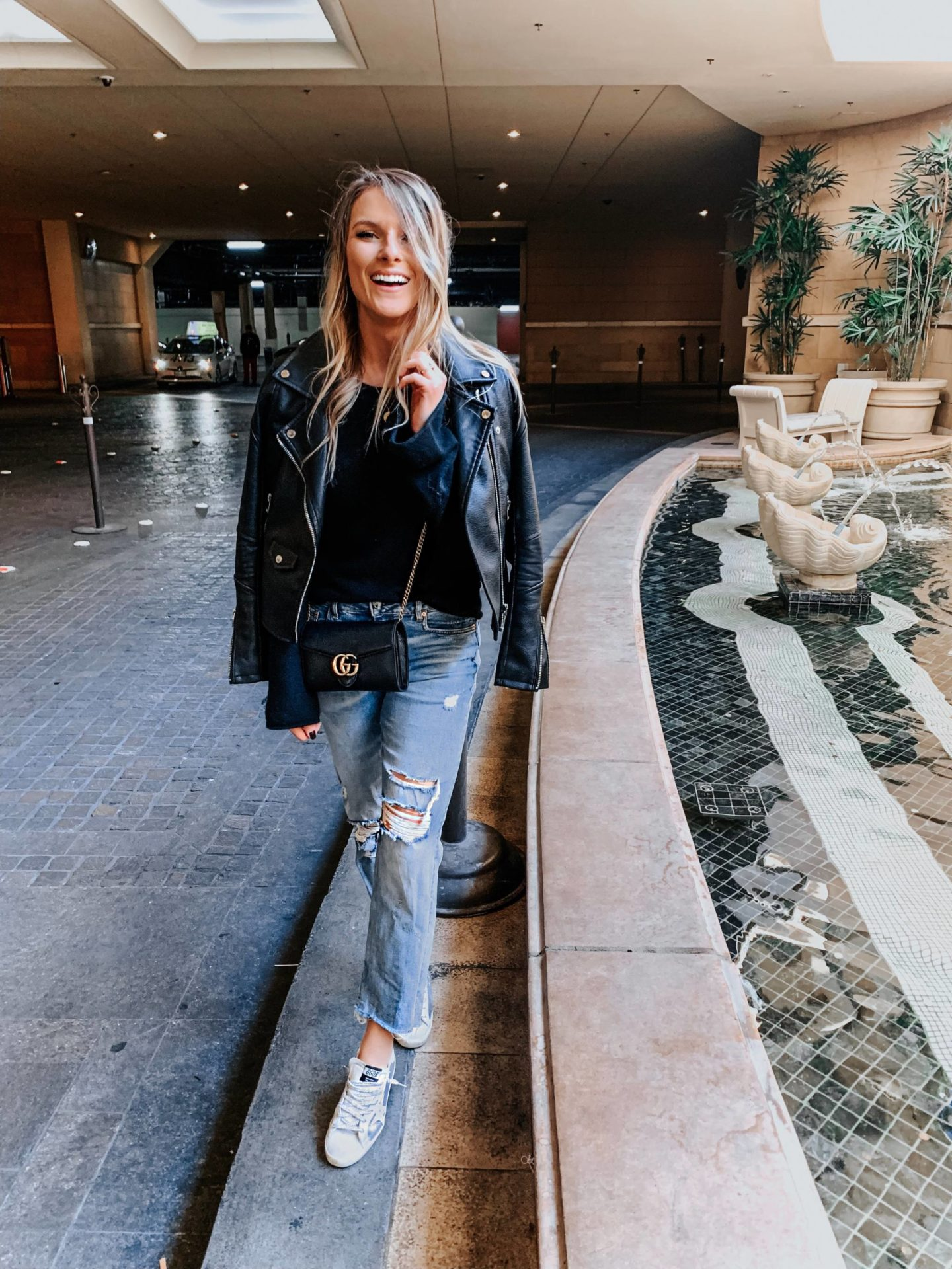 blonde girl wearing distressed denim and golden goose shoes in las vegas