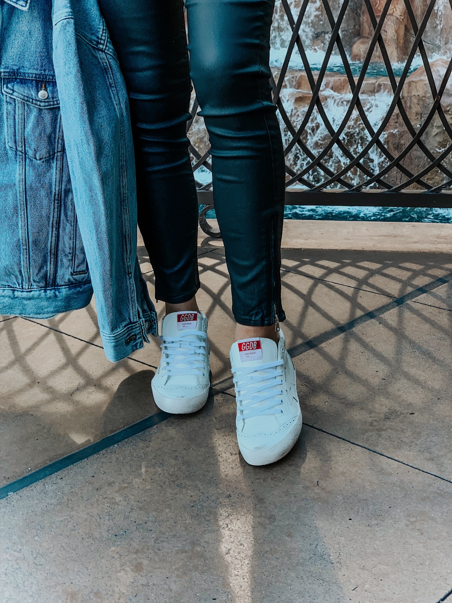 girl wearing white mid star golden goose sneakers and holding a denim jacket