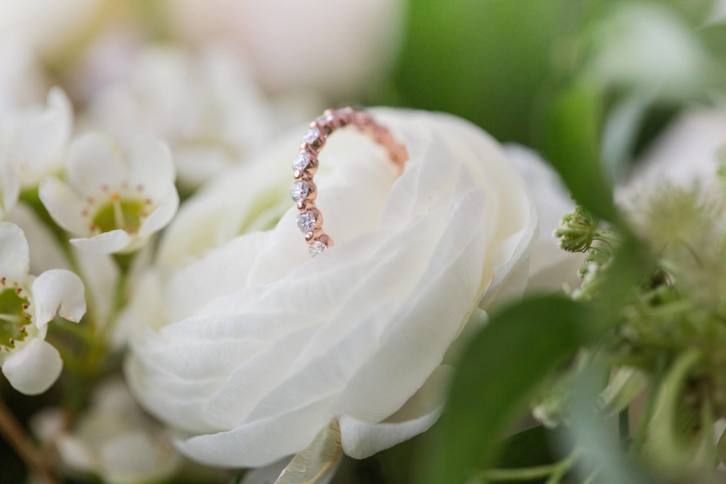 rose gold eternity band in flowers