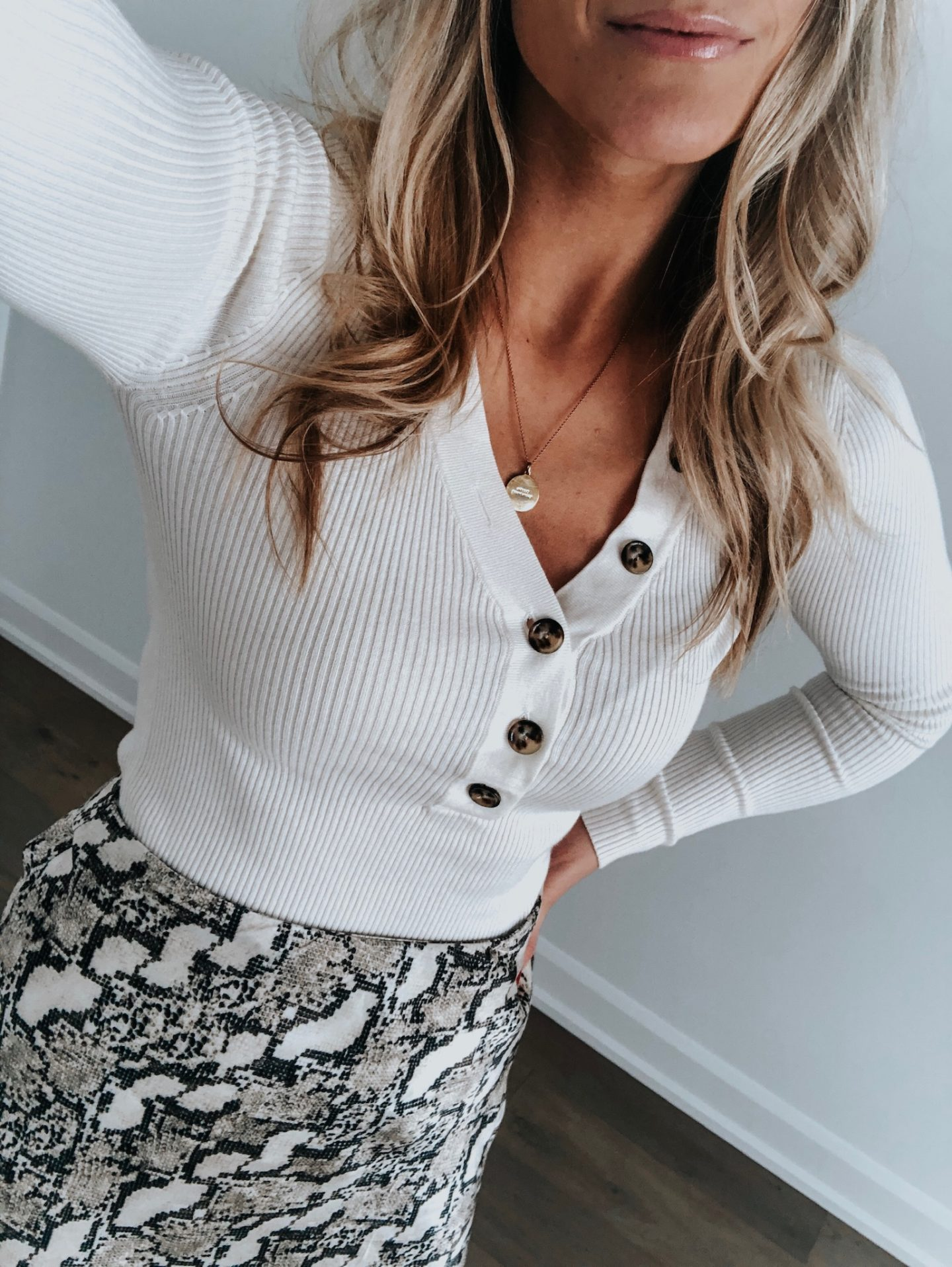 blonde girl wearing snake print skirt and white top