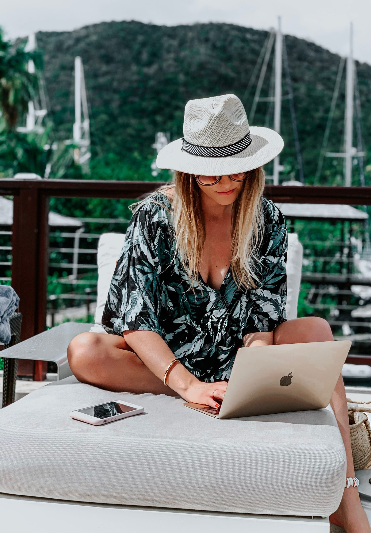 blonde wearing beach cover up using laptop