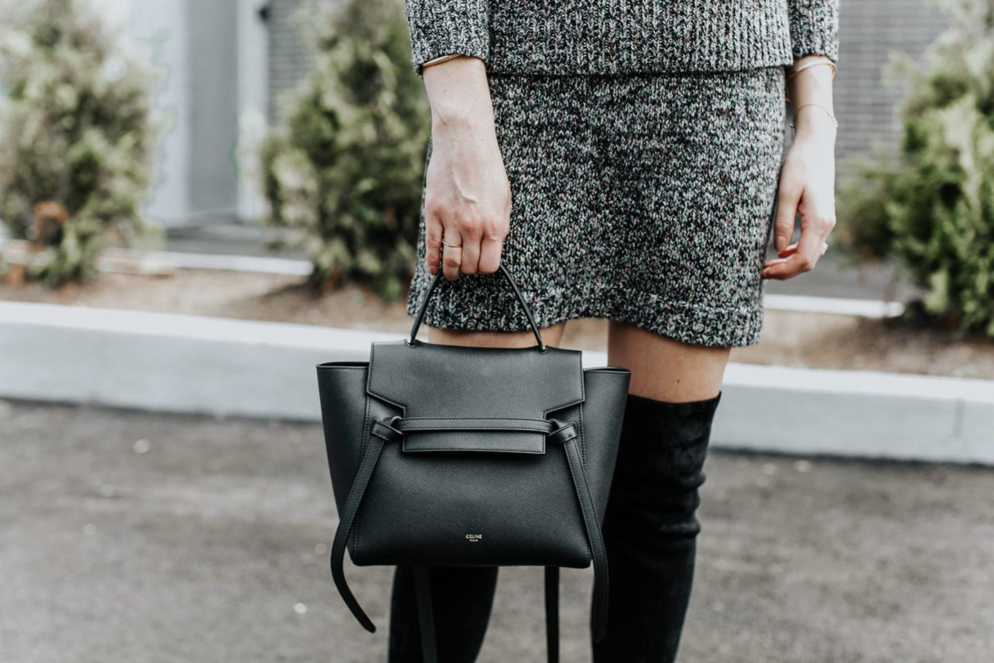 girl holding celine micro belt bag in black